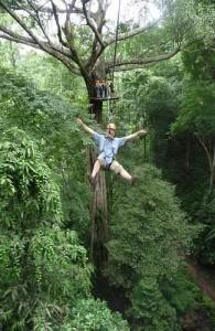 Je glijdt in het tropisch regenwoud via een kabel van boom naar boom.