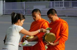 Boeddhistische monniken kleuren in de vroege ochtend het straatbeeld van Bangkok.
